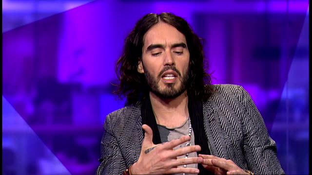 russell brand interview england london gir int russell brand through newsroom and into studio with reporter jon snow russell brand interview sot - jon snow journalist stock-videos und b-roll-filmmaterial