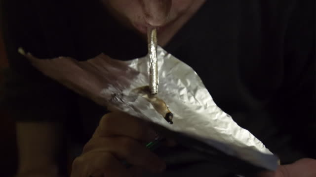 drug inhaling the the vapour from heroin that they are burning through tin foil, chasing the dragon - heroin stock videos & royalty-free footage