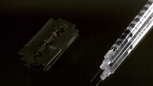 cu slo mo drug powder falling on razor blade and syringes against black background / vieux pont, normandy, france - razor stock videos & royalty-free footage