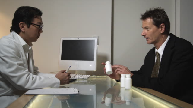 MS, Drug sales representative talking to doctor in office, Sydney, Australia
