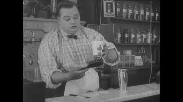1917 a drug store clerk (fatty arbuckle) makes ice cream shakes using expert and unorthodox methods - careless stock videos & royalty-free footage