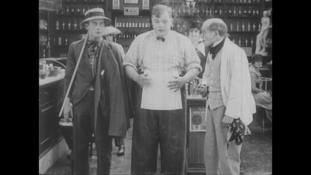 vidéos et rushes de 1917 a drug store clerk (fatty arbuckle) turns a coworker into  a human coat rack - homme soumis