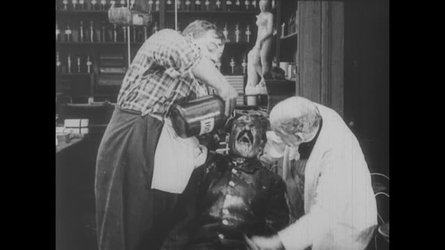 1917 a drug store owner and his clerk (fatty arbuckle) attempt to help an injured man - fatty arbuckle stock videos and b-roll footage