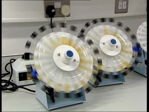 urine sample processed test tubes being spun by centrifuge / scientist looking at analysis of sample on computer screen - reagenzglas stock-videos und b-roll-filmmaterial