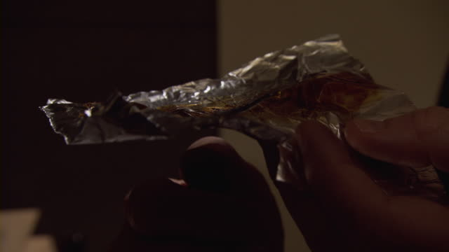 A drug user ignites a cigarette lighter under a a piece of aluminum foil with crack cocaine and holds a straw to the drug.