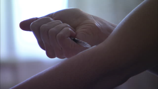 a drug user injects heroin into her arm. - injecting heroin stock videos & royalty-free footage