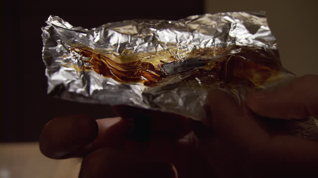 a drug user lighting up a cigarette lighter under a piece of an aluminum foil covered with crack cocaine. - cocaina video stock e b–roll
