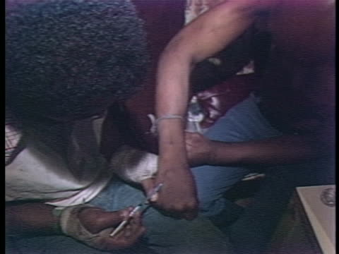stockvideo's en b-roll-footage met drug users injecting themselves with speed. there is an opening closeup shot of someone's brown skinned hand injecting drugs through a needle into... - crime or recreational drug or prison or legal trial