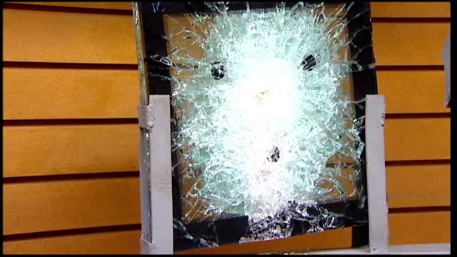 vídeos de stock, filmes e b-roll de car armouring workshop / tijuana skyline various shots of shattered pieces of bulletproof glass following gunshot tests - à prova de balas
