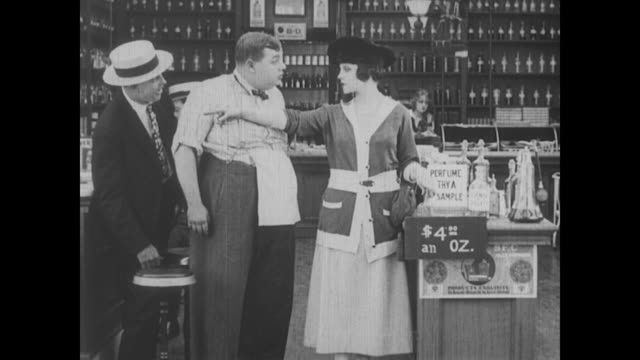1917 drugstore clerk (fatty arbuckle) tries to prevent customer from over-using perfume samples - fatty arbuckle stock videos and b-roll footage