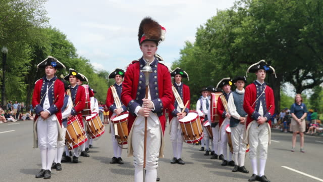 a drum and bugle corps dressed in revolutionary war fashion stops for a moment of rememberance during the national memorial day parade on memorial day - bugle stock videos and b-roll footage