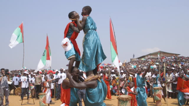 drum circle and human pyramid performance during presidential campaign rally for pierre nkurunziza in burundi wide shot - human pyramid stock videos and b-roll footage