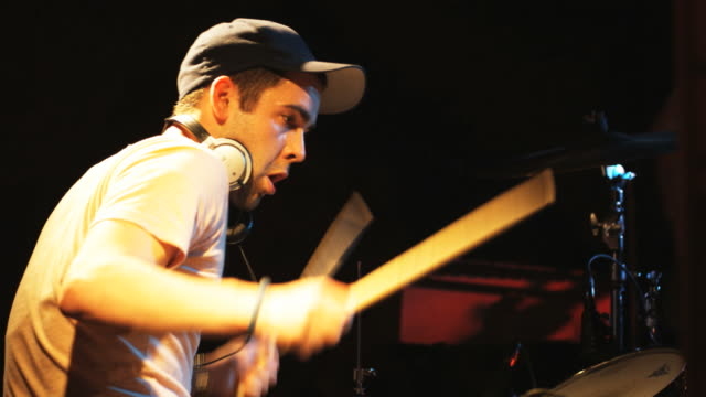 drummer playing in a rock and roll concert with a band