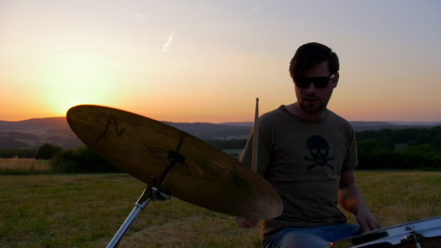 drummer plays drums in meadow at sunset - trommel stock-videos und b-roll-filmmaterial