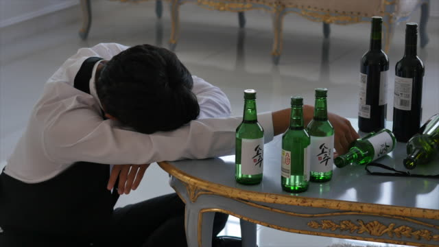 drunk groom sleeping next to empty alcohol bottles - drunk stock videos & royalty-free footage