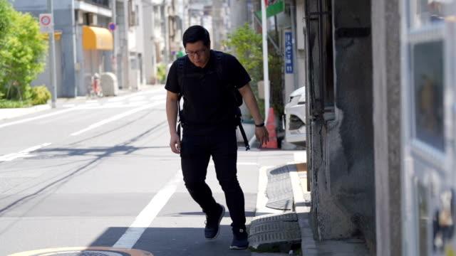 酔っぱらった若いアジア人男性が通りを歩きながらぐるぐる回る - 疑念点の映像素材/bロール