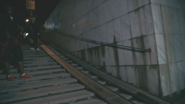 Drunk man running along ramp of underground walkway
