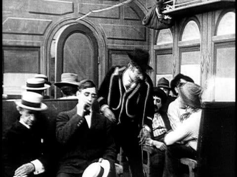 1910 b&w drunk man staring fight in train/ usa - 1910 stock-videos und b-roll-filmmaterial