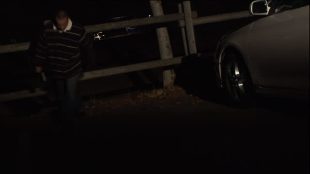 a drunk partygoer climbs through a fence and staggers to his car. - drinking and driving stock videos & royalty-free footage