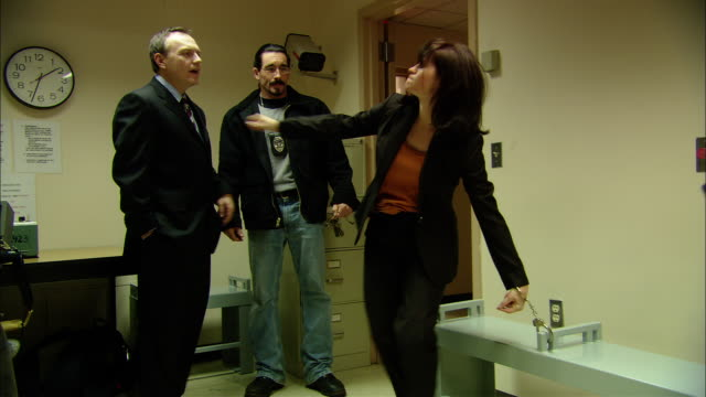 vídeos y material grabado en eventos de stock de ms drunk woman handcuffed to bench in police station trying to stand up, then sitting back down as two officers attempt to calm her down/ new jersey - perilla