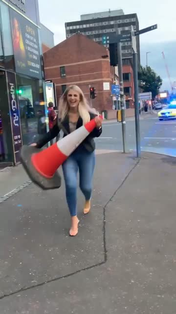 drunk woman tries to steal the orange traffic cone outside on the sidewalk. before she can run away, a police car turns on its lights and sirens and... - pavement stock videos & royalty-free footage