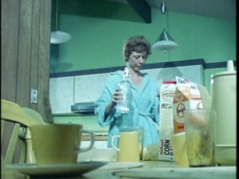 stockvideo's en b-roll-footage met 1971 ms drunk woman with drink bumping into kitchen table, los angeles, california, usa, audio  - alcoholisme