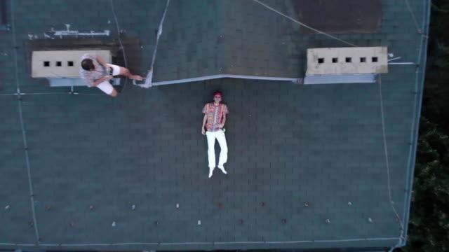 betrunkener junger mann liegt auf dem dach - 25 29 jahre stock-videos und b-roll-filmmaterial