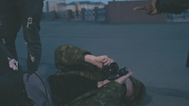 Drunken man lying on asphalt and taking pictures
