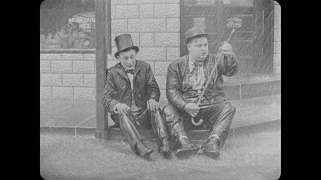 1918 drunken man (fatty arbuckle) tries to act sober in front of cop - kopf schütteln stock-videos und b-roll-filmmaterial