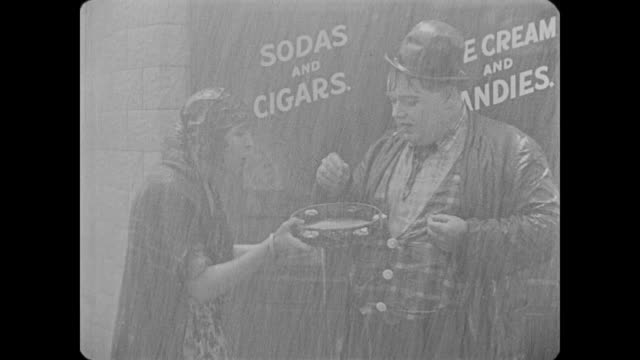 1918 drunken man (fatty arbuckle) tries to light cigarette under rainy policeman's cap - waterproof clothing stock videos & royalty-free footage