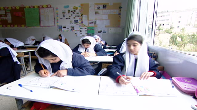 druze schoolgirls in traditional attire wearing mandils a type of headscarf and writing in textbooks at irfan a druze religious school with five... - theology stock videos & royalty-free footage