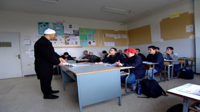druze sheikh teacher opening a textbook in a classroom of teenage boys. irfan is a druze religious school with five branches in lebanon that operate... - teenage boys stock videos & royalty-free footage