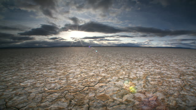 dry, cracked earth and clouds - terra brulla video stock e b–roll