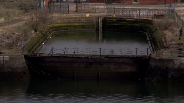 a dry dock filled with water sits in belfast's titanic quarter with the historic headquarters of harland and wolff shipbuilders. available in hd. - titanic belfast stock videos & royalty-free footage