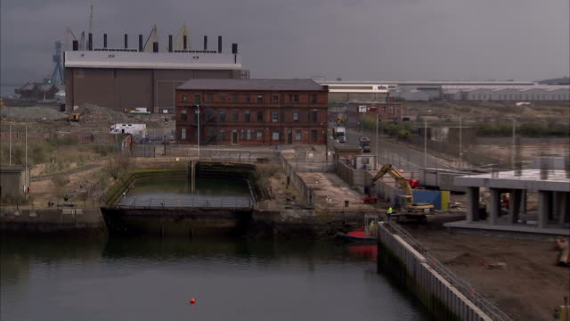 a dry dock, the former harland and wolff headqurters and the historic paint hall stands next to construction sites in belfast's titanic quarter. available in hd. - titanic belfast stock videos & royalty-free footage