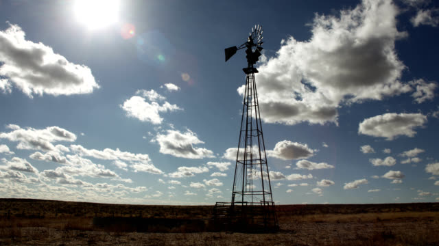 Dry grasslands windmill cloudscape sun lens flare time-lapse Yuma County prairie Colorado