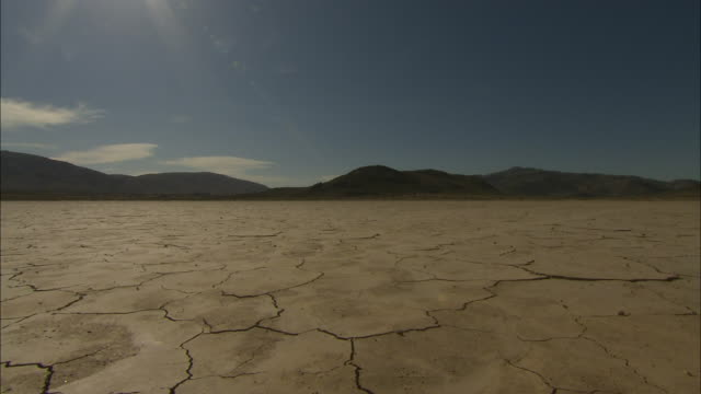 A dry lake bed gives way to a mountainous horizon.
