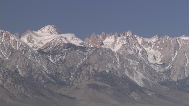 a dry lake rests below the sierra nevada range. - californian sierra nevada stock videos & royalty-free footage