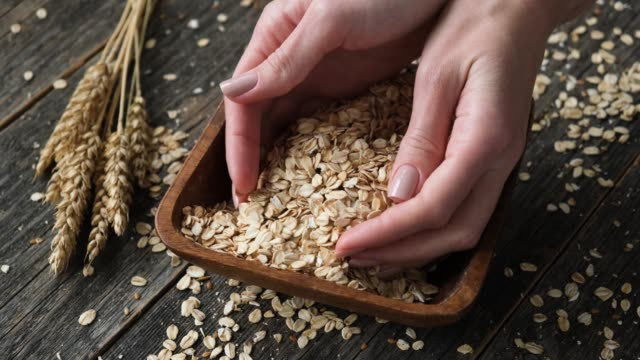 dry oat flakes, organic rolled oats in wooden bowl - oatmeal stock videos & royalty-free footage