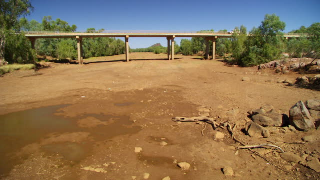 ws dry riverbed bridge with car crossing / cloncurry, queensland, australia - 乾的 個影片檔及 b 捲影像