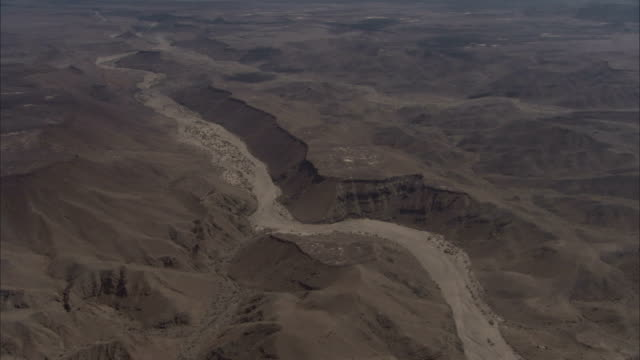 A dry riverbed winds through a volcanic landscape. Available in HD.