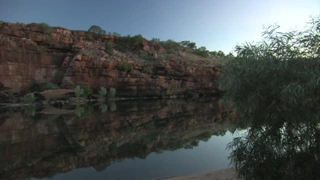 dry, rocky landscape along a river. sandstone cliffs reflected in water. - sandstone stock videos & royalty-free footage
