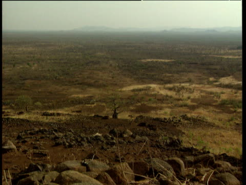 dry rocky landscape zoom in to column of sudan peoples' liberation army soldiers climbing up hillside - tetto di paglia video stock e b–roll