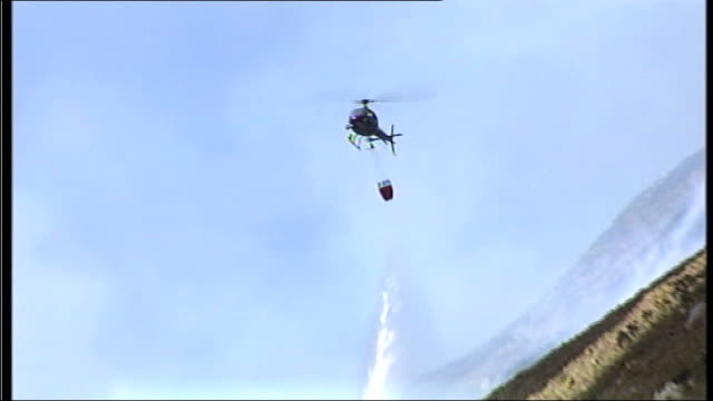 dry spell sparks wildfires across the uk scotland aberdeenshire balmoral helicopter dropping water on fires smoke rising from behind hillside sean... - aberdeenshire stock videos & royalty-free footage