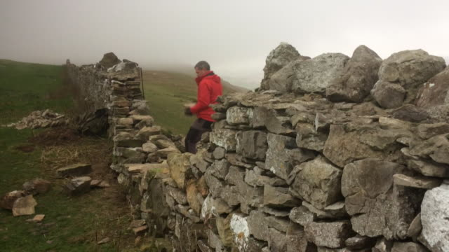 dry stone wall being repaired in great orme wales - stone wall stock videos & royalty-free footage