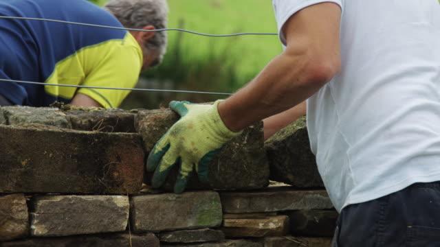 dry stone wall builders testing blocks - stone wall stock videos & royalty-free footage