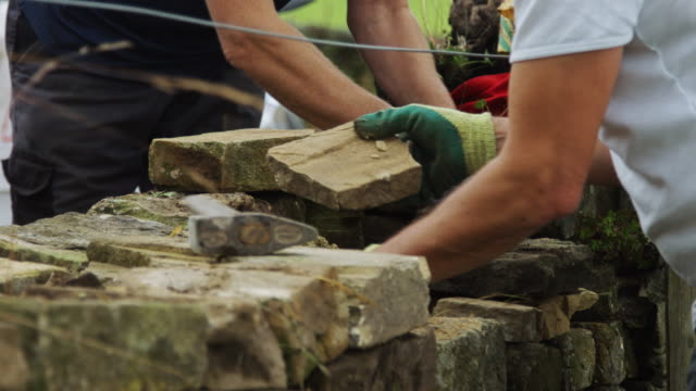 dry stone wall repairers - stone wall stock videos and b-roll footage