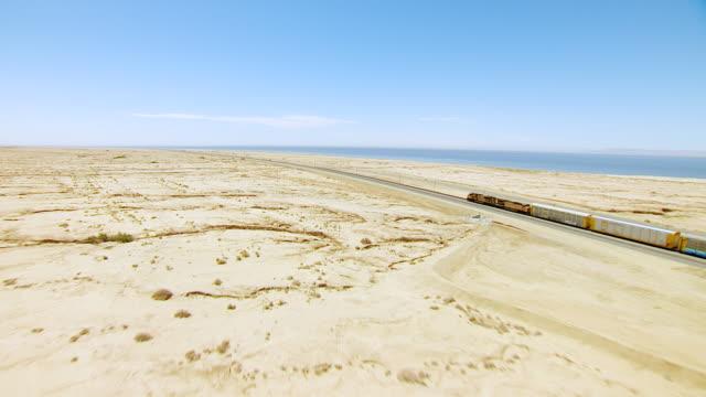 ws aerial pov dry stream beds in desert and freight train on railroad with shoreline of salton sea in background / california, united states - ökenklimat bildbanksvideor och videomaterial från bakom kulisserna
