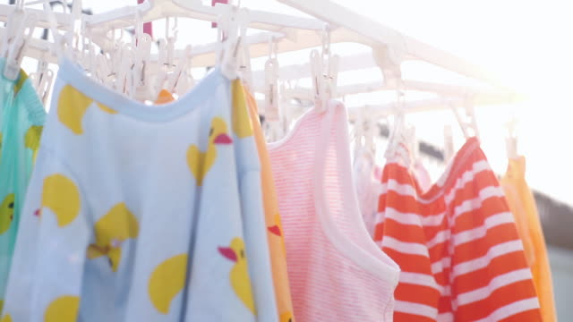 drying baby colorful clothes hanging on the clip outdoors. - laundry stock videos & royalty-free footage