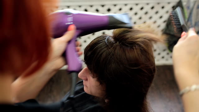 drying hair and styling a new hairstyle. - blow drying hair stock videos and b-roll footage